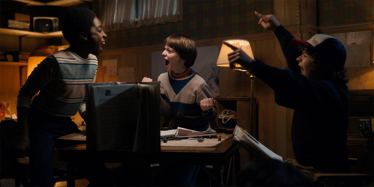 The boys from Stranger Things sit around a table in Mike's basement playing D&D